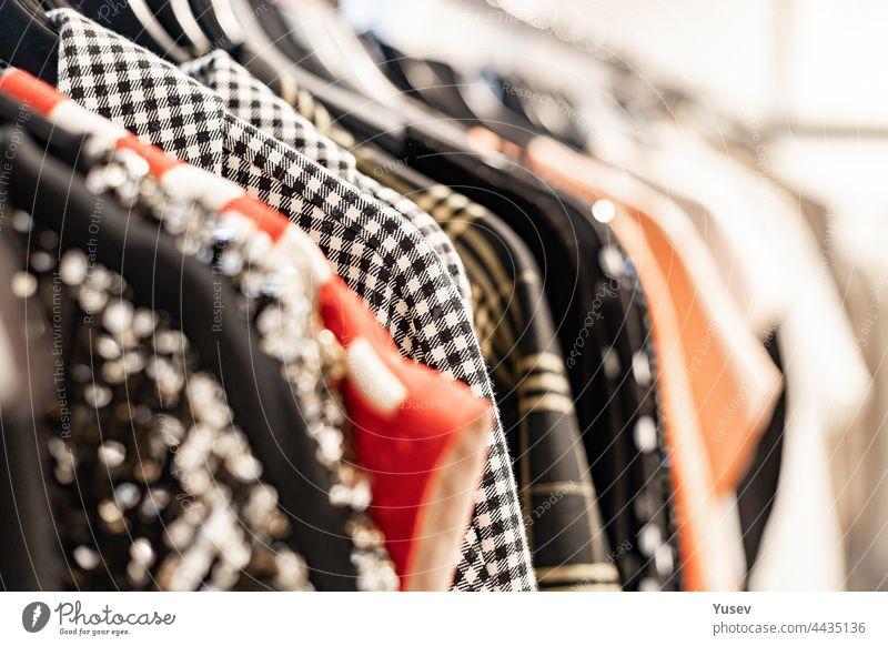 Modische, stilvolle Frauenkleidung auf einem Kleiderbügel. Nahaufnahme von Markenkleidung in einem Ausstellungsraum. Heller Hintergrund. Mode-Einzelhandel, Show-Raum, Einkaufen oder saisonalen Verkauf Konzept. Selektiver Fokus