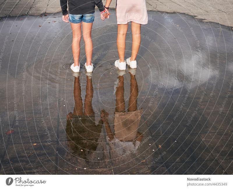 Rückansicht von zwei Mädchen, die sich an den Händen halten und auf einer Wasserpfütze stehen, es werden keine Gesichter gezeigt Teenager jung Frau Zusammensein