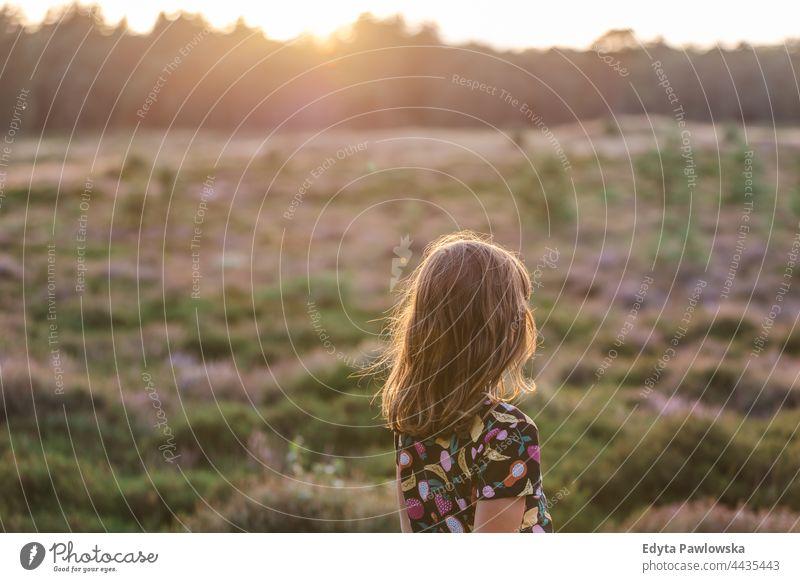 Kleines Mädchen auf einer Wiese voller Heidekraut bei Sonnenuntergang Gras Feld ländlich Landschaft Abenteuer Wildnis wild Haare Urlaub reisen aktiv Sommerzeit