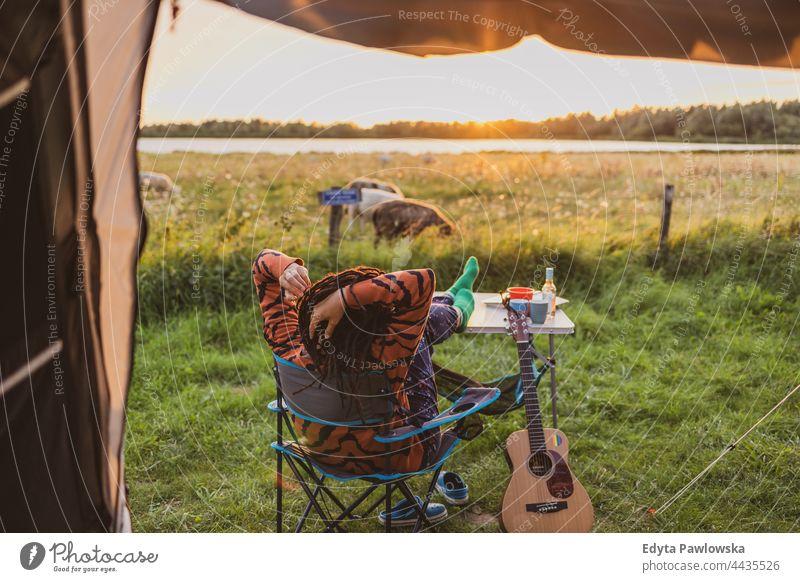 Frau entspannt sich bei Sonnenuntergang vor dem Zelt Campingplatz Wiese Gras Feld ländlich grün Landschaft Abenteuer wandern Wildnis wilder Urlaub reisen aktiv