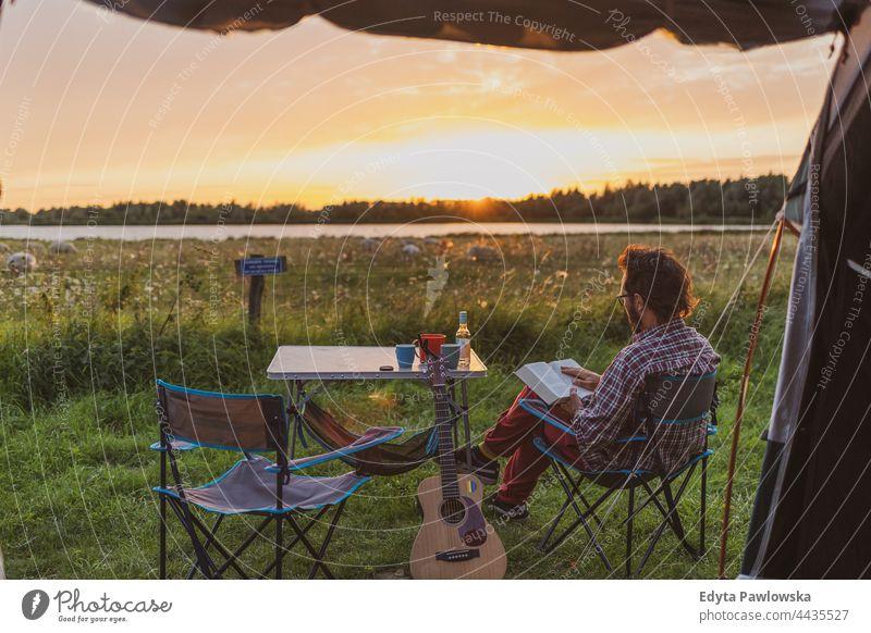 Mann liest ein Buch auf einem Campingplatz. Blick aus einem Zelt Wiese Gras Feld ländlich grün Landschaft Abenteuer wandern Wildnis wilder Urlaub reisen aktiv