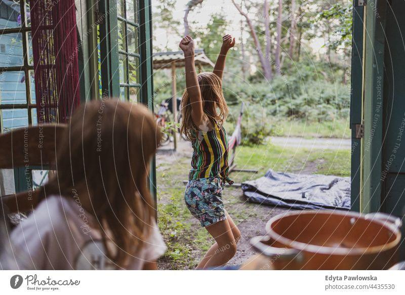 Spielende Kinder in der Gartenlaube Gartenhaus Cottage heimwärts Haus Hinterhof Tanzen spielerisch Freude Familie niedlich Mädchen wenig Glück Kindheit Spaß