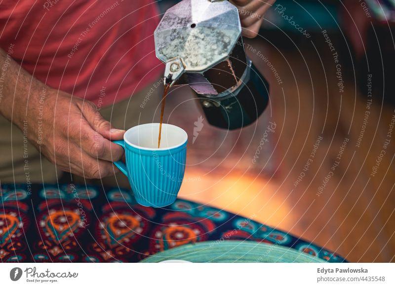 Mann gießt Kaffee aus einer Kaffeemaschine in eine Tasse Kaffeetasse Hände trinken Lebensmittel frisch Frische Gießen Barista Herstellung heimwärts Haus