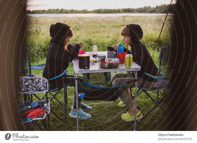 Kinder beim Essen vor dem Zelt auf einem Campingplatz Familie Lebensmittel Wiese Gras Feld ländlich grün Landschaft Abenteuer wandern Wildnis wilder Urlaub