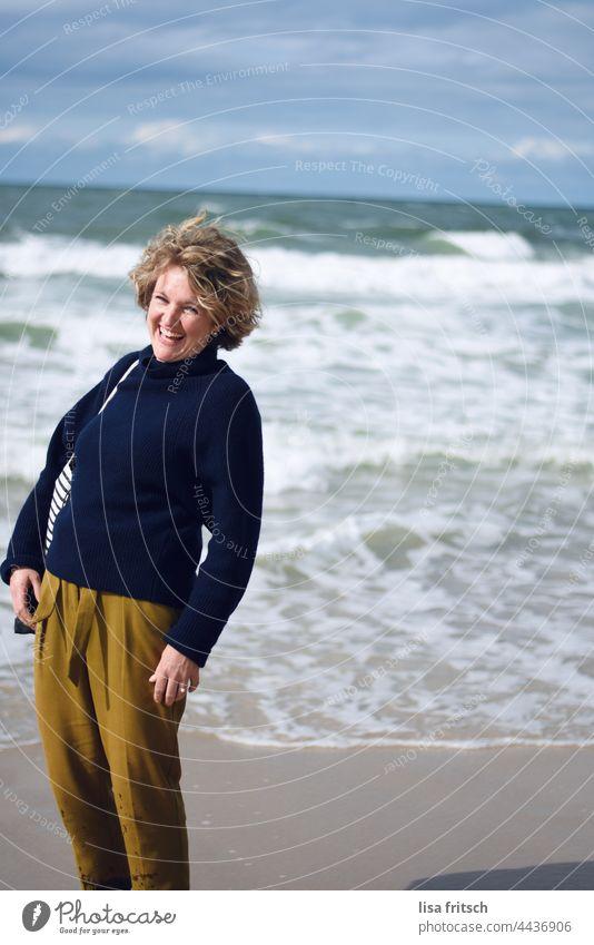 GUTE LAUNE - WAS WILL MAN MEHR - LACHENDE FRAU Farbfoto Ferien & Urlaub & Reisen Frau 30-45 Jahre Erwachsene Außenaufnahme Meer Wellen gutes Wetter Herbst Sylt