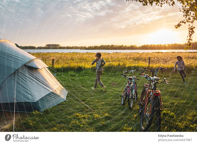 Spielende Kinder auf dem Campingplatz rennen spielerisch Spaß Freude Familie Zelt Fahrrad Fahrradfahren Wiese Gras Feld ländlich grün Landschaft Abenteuer
