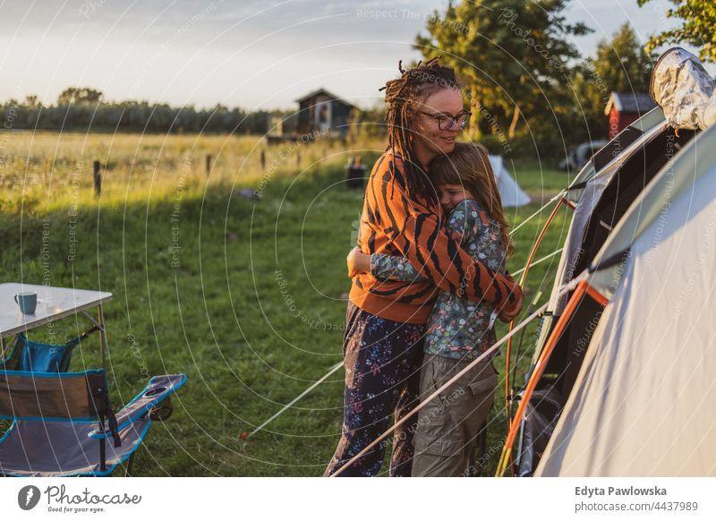 Mutter und Tochter umarmen sich vor dem Zelt auf dem Campingplatz Eltern Zusammensein Liebe umarmend Spaß Freude Kinder Familie Fahrrad Fahrradfahren Wiese Gras