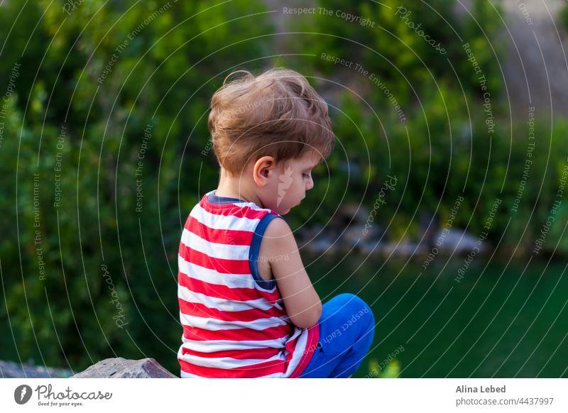 Ein Kind sitzt auf dem Gipfel eines schönen Canyons und betrachtet das Wasser darin. Das Ufer der Schlucht. Kindheit reisen Person Vorschein Frau Hintergrund