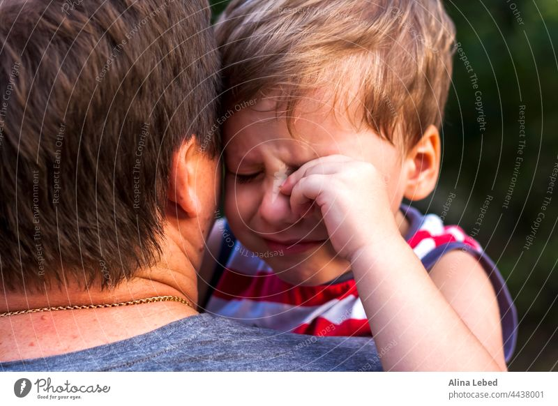Ein kleiner Junge weint in den Armen seines Vaters und kuschelt sich an ihn, um sich beschützt zu fühlen. Ausdruck fürsorglich Weinen Partnerschaft Kind Sohn