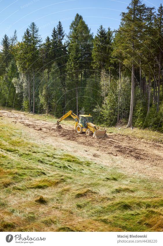 Ein Bagger ebnet die Oberfläche eines Hügels für eine Skipiste. Baggerlader Berge u. Gebirge Berghang Wald Natur Planierraupe Gerät im Freien Konstruktion