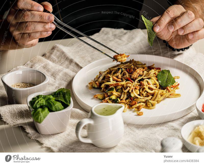 Traditionelle Nudeln mit Meeresfrüchten. Der Küchenchef bereitet eine Pasta Marinara zu. Der Chefkoch dekoriert das Gericht mit einer Pinzette. Spaghetti mit Meeresfrüchten. Mediterrane Küche. Menschen bei der Arbeit. Nahaufnahme. Körperteile