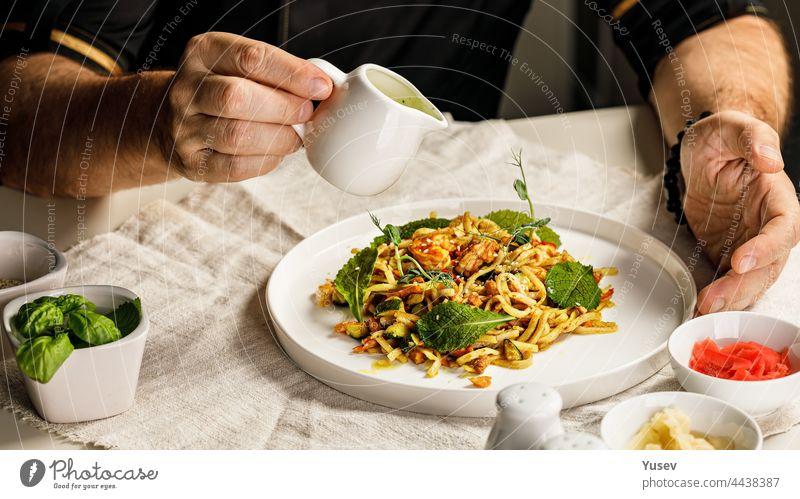 Spaghetti mit Meeresfrüchten. Die Hände des Chefkochs bereiten eine traditionelle Pasta mit Meeresfrüchten zu. Der Koch gießt die Soße über das Gericht. Restaurant serviert Gericht. Mediterrane Küche Banner