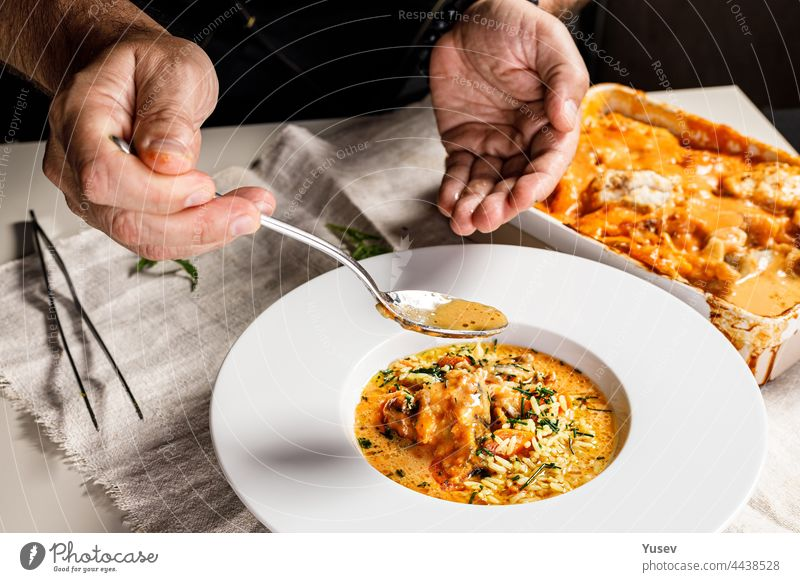 Authentische spanische Paella mit Kabeljau und Muscheln. Ein traditionelles mediterranes Gericht mit Meeresfrüchten. Der Chefkoch bereitet das Gericht zu. Ein Restaurant serviert das Gericht. Nahaufnahme. Menschen bei der Arbeit. Körperteile