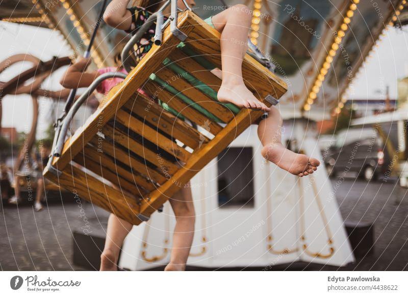 Kinder haben Spaß auf einem Karussell Fuß nackte Füße Kinderkarussell Reiten Schaukeln Messegelände lustig Zusammensein Vergnügungspark Urlaub Abenteuer