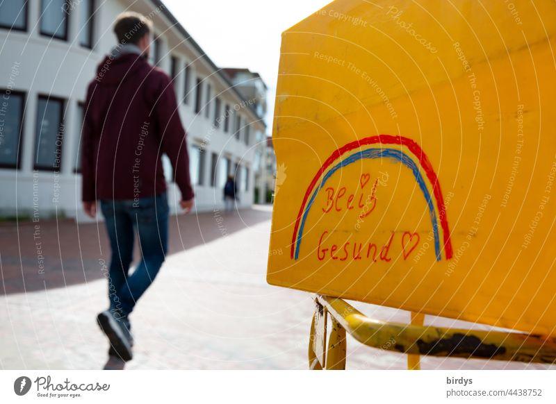 Bleib gesund ! Aufschrift mit Regenbogen auf einer gelben Box. Im Hintergrund geht ein junger Mann vorbei. Corona, Pandemie, Impfen Covid19 Impfung Gesundheit