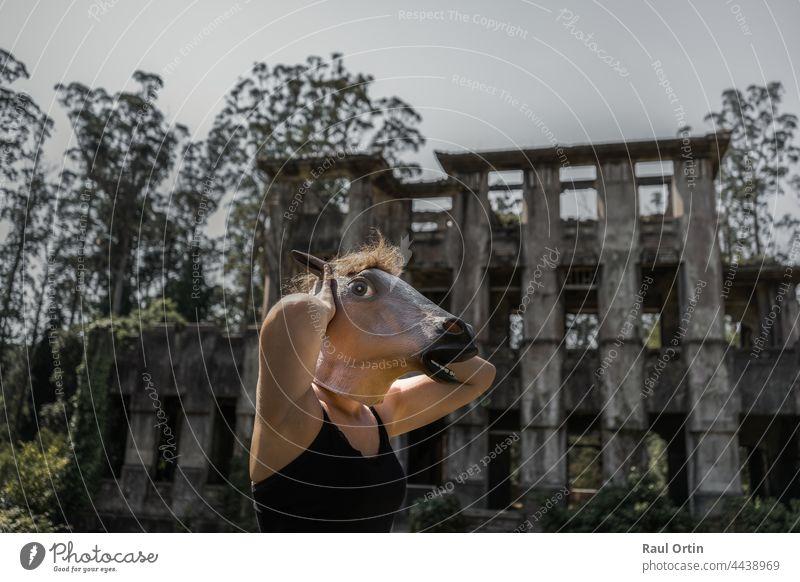 Frau in Pferdemaske mit Händen im Kopf vor einem verlassenen Horrorhaus. ängstlich Halloween Mundschutz alt Herrenhaus Angst Entsetzen Verlassen Haus
