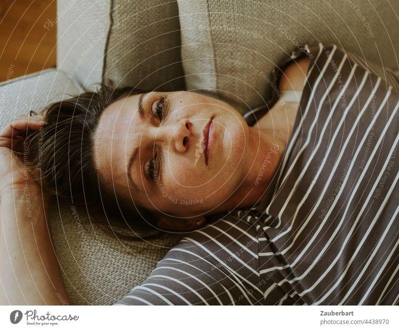 Porträt einer schönen Frau im gestreiften Oberteil, auf Sofa liegend Portrait weiblich Blick Kissen Ruhe ruhig ausruhen entspannen Erholung gemütlich Wohnzimmer