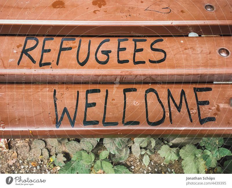 Refugees Welcome, Flüchtlinge willkommen als Schrift auf einer Bank Wörter Wort Aussage Aufforderung auffordern Typografie Typographie Buchstaben geschrieben