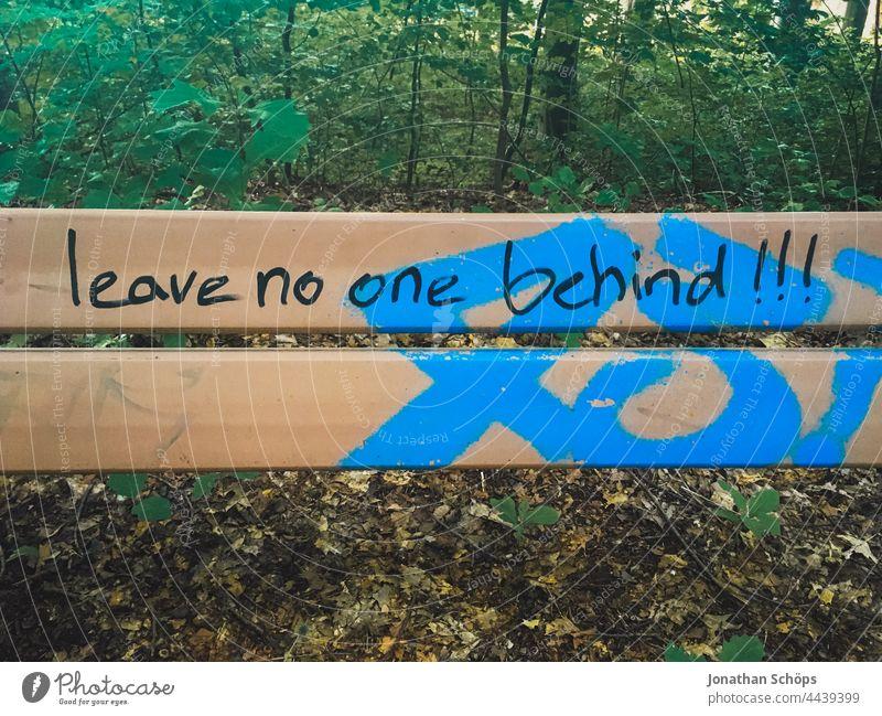 Leave no one behind!!!, lass niemanden zurück als Schrift auf einer Bank Wörter Wort Aussage Aufforderung auffordern Typografie Typographie Buchstaben