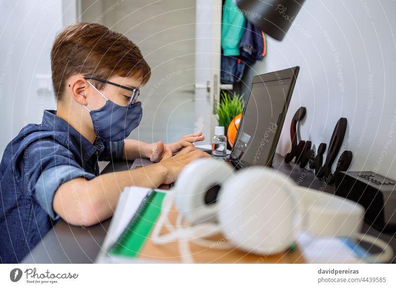 Teenager mit Gesichtsmaske macht Hausaufgaben mit Laptop Schule zu Hause Coronavirus Heimunterricht E-Learning Junge covid-19 Sperrung Schutzmaske Brille Tippen