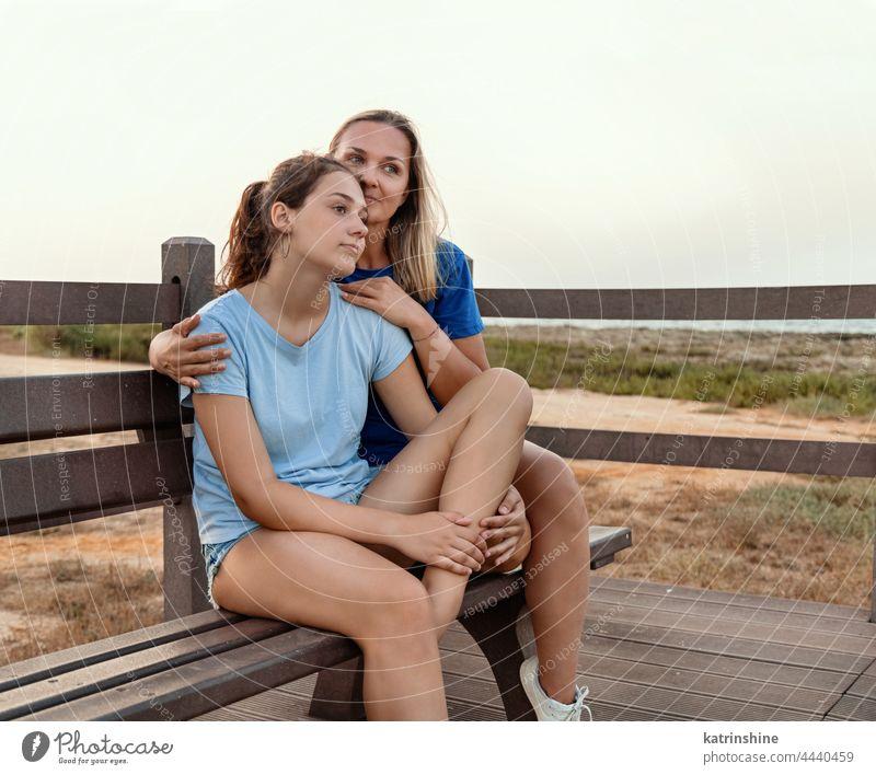 Mutter und Tochter sitzen bei Sonnenuntergang zusammen auf einer Bank Frau Attrappe Teenager umarmend T-Shirt Umarmung Lächeln Jugendlicher blau