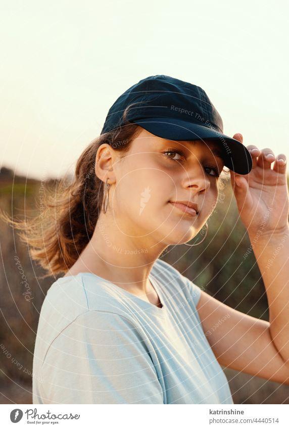 Teenager-Mädchen mit dunkelblauer Baseballmütze und T-Shirt im Freien Jugendlicher Landschaft abgelegt Kaukasier Attrappe visier tragend T-Shirts Kindheit Frau