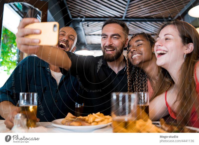 Eine Gruppe von Freunden macht ein Selfie mit einem Mobiltelefon in einem Restaurant. Zusammensein trinken Bier Mobile Telefon Lebensmittel Mahlzeit