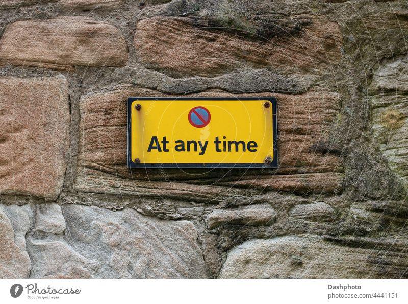 """Schild """"Parken zu jeder Zeit verboten"""" an einer alten Steinmauer im Stadtzentrum Zeichen Hinweisschild Verkehrsschild Verkehrsgebot Hinweisschild am Straßenrand"""