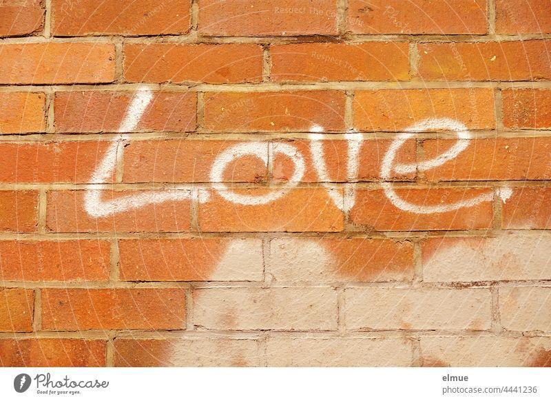 Love steht in weißen Buchstaben an der roten Ziegelmauer / Graffito love Liebe Graffiti Schrift sprayen Wort englisch Liebeserklärung Liebesbeweis Kreativität