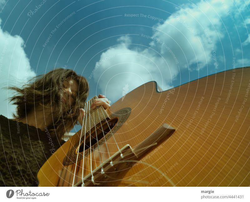 Gitarrenspielerin unter blauen Himmel mit Wolken Musikinstrument Saiteninstrumente Freizeit & Hobby musizieren Gitarrensaite Detailaufnahme Nahaufnahme Musiker