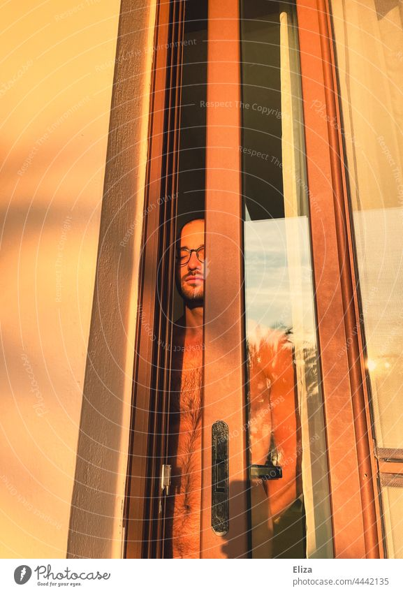 Nackter Mann steht in der Balkontür und genießt mit geschlossenen Augen die Morgensonne nackt geschlossene Augen morgens Sonnenlicht träumen genießen