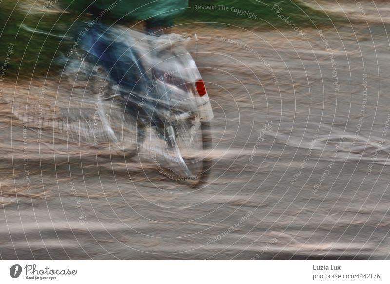 Geschwindigkeit, unterwegs wie im Traum: ein Radfahrer abwärts nach links in einer herbstlichen Allee Radler verschwommen schnell Herbst von hinten Rücklicht