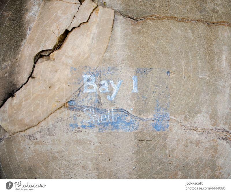 Bay 1 Shell Bezeichnung auf rissiger Mauer historisch alt Beschriftung Englisch Schriftzeichen Schablonenschrift Detailaufnahme Wort verwittert brüchig