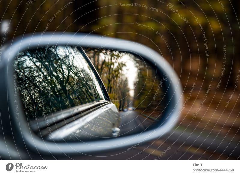 eine Herbstliche Landstraße im Rückspiegel des Autos Farbfoto Straße PKW Menschenleer Verkehr Außenaufnahme Landschaft Baum Spiegel fahren Autofahren
