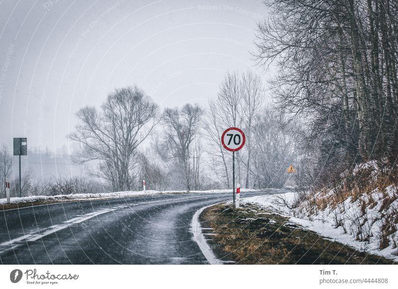 die Kurve einer Landstraße im Winter. Im Vordergrund ein Verkehrsschild 70 Polen Straße Schnee Außenaufnahme kalt Menschenleer Baum Landschaft Natur