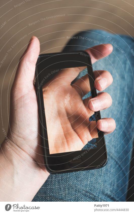 Nahaufnahme einer Hand die ein Smartphone hält, auf dessen Display die Hand durchscheinend zu sehen ist, die es hält Handy halten Lifestyle Telefon