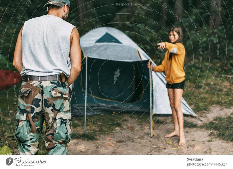 Ein glücklicher Vater und seine Tochter bauen ein Campingzelt auf. Familienzeit, Familienerholung, Pflege Zelt Installation Glück wenig männlich Eltern