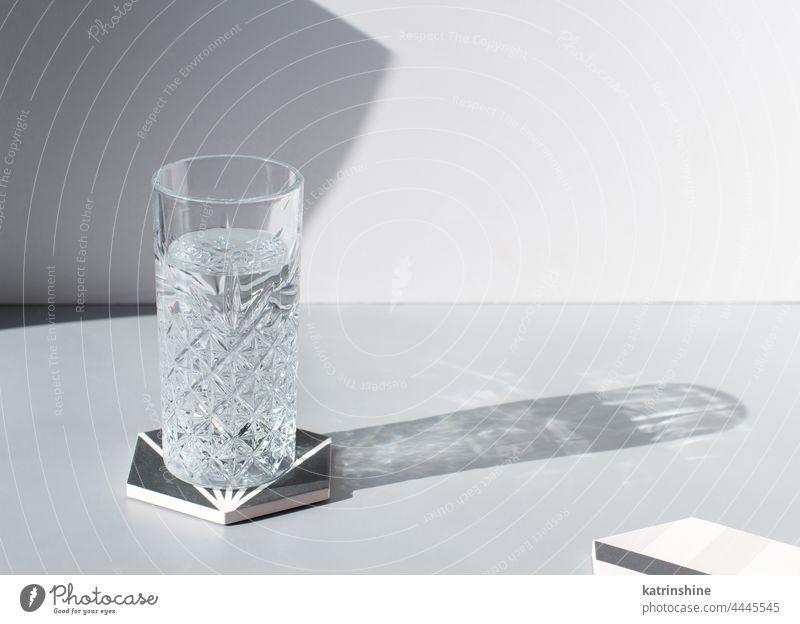 Facettiertes Trinkglas mit frischem, sauberem Wasser mit Schatten auf grauem Tisch, Kopierraum Glas trinken Glaswaren hartes Licht übersichtlich satt Sommer