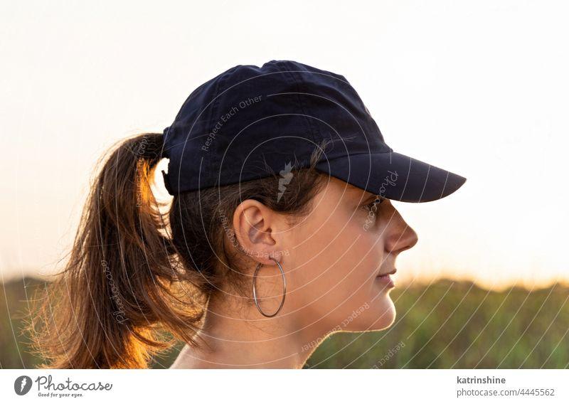 Teenager-Mädchen mit dunkelblauer Baseballmütze bei Sonnenuntergang im Freien Jugendlicher Kaukasier Attrappe visier Kopf tragend Kindheit Frau Fröhlichkeit