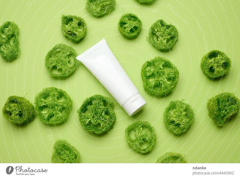 Leere weiße Kunststofftuben für Kosmetika auf grünem Hintergrund. Verpackung für Creme, Gel, Serum, Werbung und Produktförderung, Draufsicht Loofah Dekor