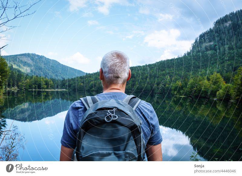 Mann mit einem Rucksack steht an einem See und genießt die Aussicht wandern Rückansicht Ausflug Tourismus Ferien & Urlaub & Reisen Freiheit Senior graue Haare