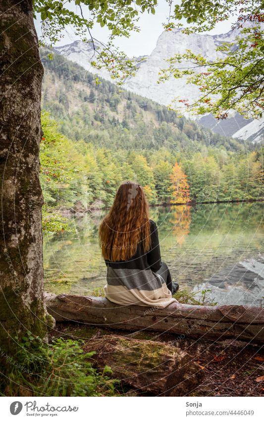 Junge Frau mit langen roten Haaren sitzt an einem See und genießt die Aussicht jung Seeufer sitzen Baumstamm Wald Herbst Rückansicht lange Haare gelockt schön