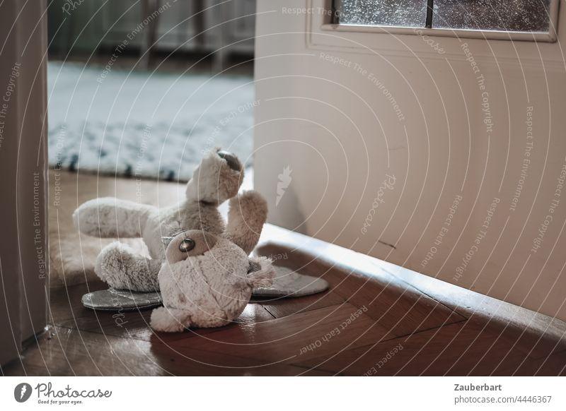 Teddybär liegt in halb geöffneter Tür zum Kinderzimmer Spielzeug liegen Kindheit Angst Missbrauch Stofftier Traurigkeit traurig Einsamkeit Trauer Aufräumen