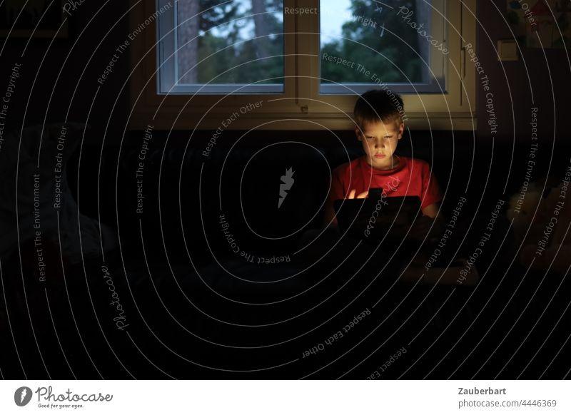 Kleiner Junge sitzt mit Tablet in dunklem Zimmer vor Fenster klein spielen dunkel rot Kind Tablet Computer Kindheit digital Internet Medienkompetenz
