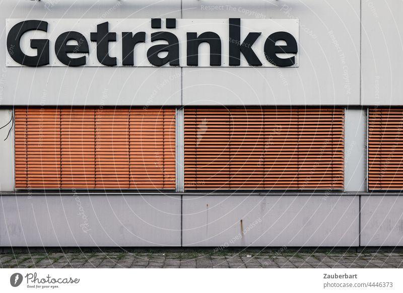 Getränke Aufschrift an Gebäude mit Betonwand mit orangen Jalousien geschlossen Wand Mauer Fassade Bauwerk grau trist geometrisch Architektur abstrakt