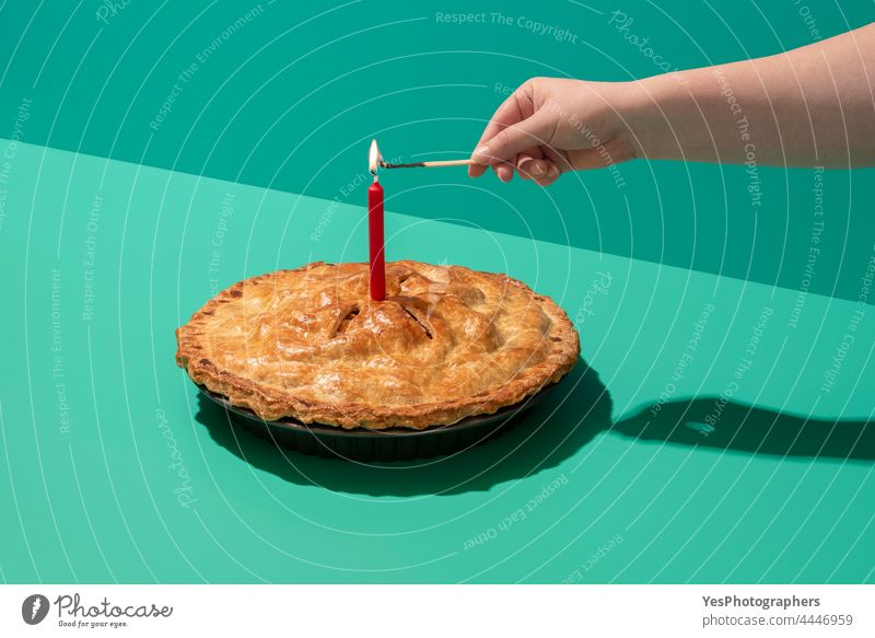 Festlicher Apfelkuchen mit einer brennenden Kerze, minimalistisch auf einem grünen Tisch 4. Juli Amerikaner Herbst Hintergrund gebacken Bäckerei Geburtstag hell