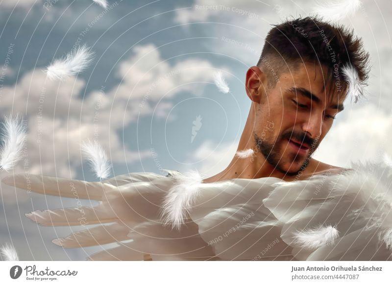 Engel. Junger Mann mit weißen Flügeln und einem blauen Himmel mit weißen Wolken im Hintergrund. Kunst Phantasie magisch jung göttlich Erzengel engelsgleich