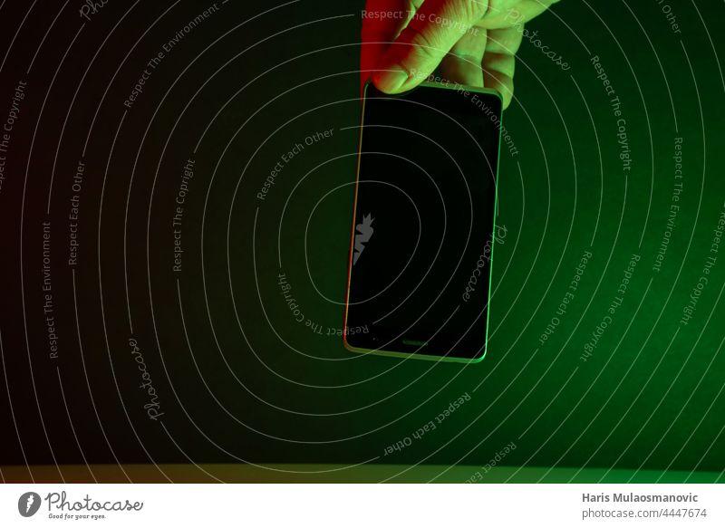 Hand hält Mobiltelefon, grüne Lichter dunkler Hintergrund süchtig App Anwendung schwarz schwarzer Hintergrund blau Funktelefon Nahaufnahme dunkel Gerät digital