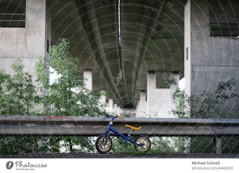 Altes Laufrad an einer Leitplanke unter einer Autobahnbrücke Kind Kindheit Außenaufnahme Bewegung Kleinkind Fahrrad Spielen früher vergangen Vergangenheit