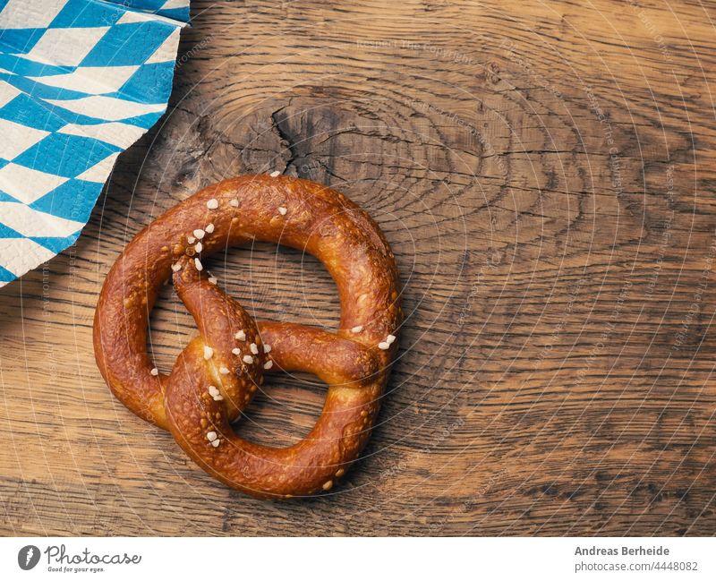 Leckere Brezel mit bayerischer Fahne auf einem rustikalen Holztisch Deutschland München Oktoberfest Bayern verdrillt knackig Originalität Gebäck lecker